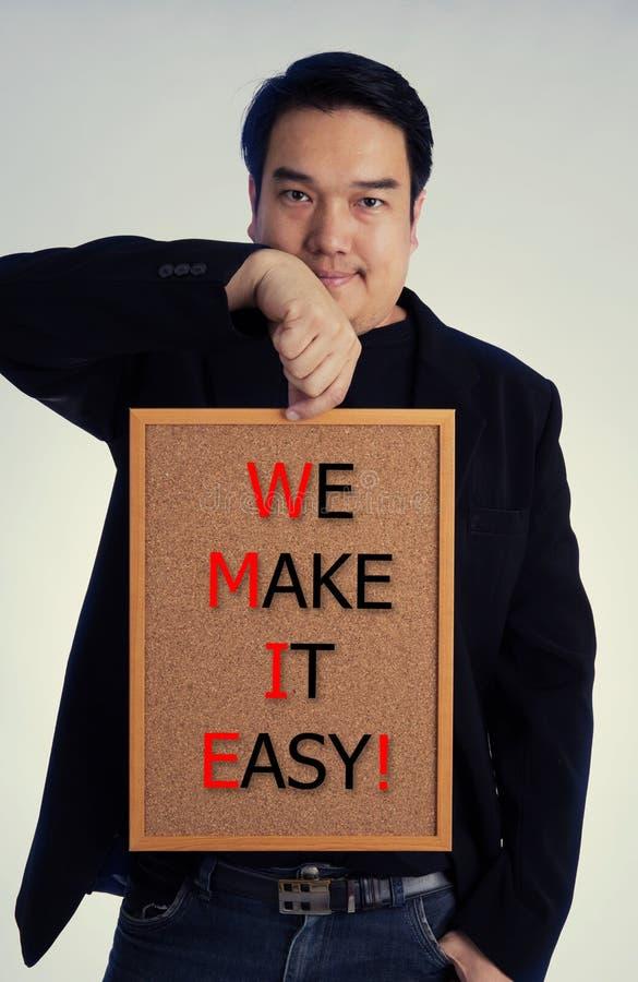 Den asiatiska mannen i svart dräkt med GÖR VI IT LÄTT! meddelande på vit b royaltyfri fotografi