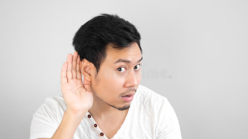 Den asiatiska mannen lyssnar till något försiktigt royaltyfria foton