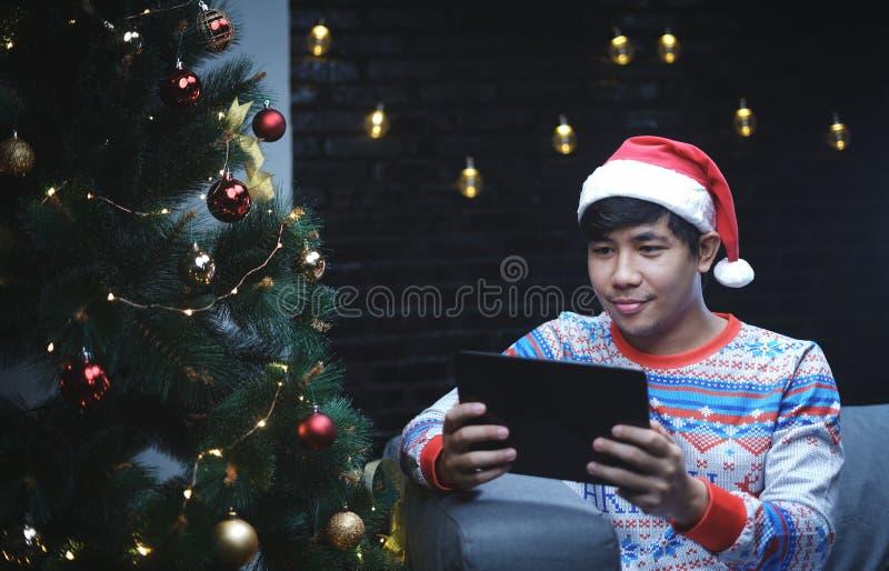 Den asiatiska mannen med juldräkten genom att använda minnestavlaapparaten som sitter är arkivfoto