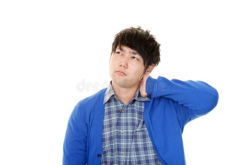 Den asiatiska mannen som har en skuldra, sm?rtar fotografering för bildbyråer