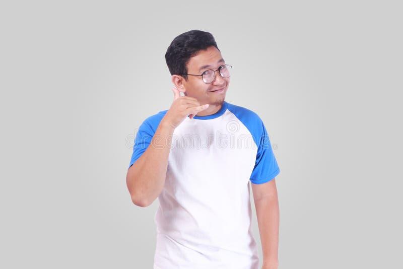 Den asiatiska mannen som ler och gör en gest, kallar mig telefontecknet arkivbild