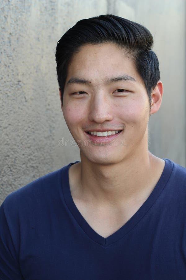 Den asiatiska mannen som ler på en grå bakgrund - lagerföra bilden arkivbild