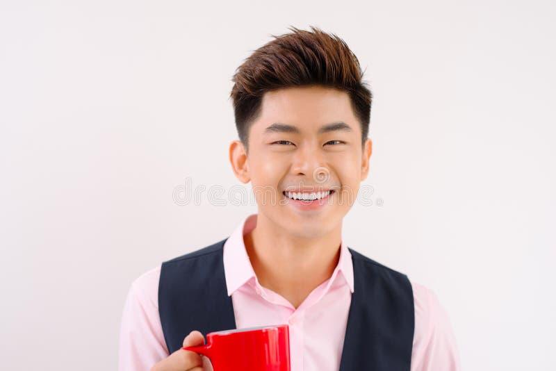 Den asiatiska mannen tar en smutt av kaffe i röd kopp arkivfoto