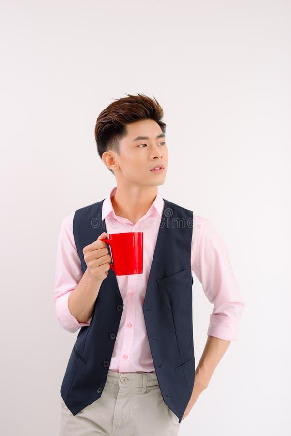 Den asiatiska mannen tar en smutt av kaffe i r?d kopp royaltyfri fotografi