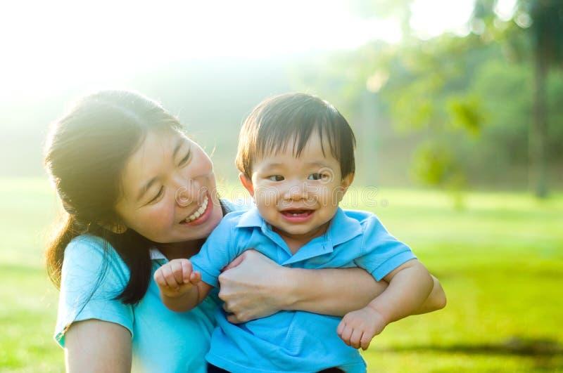 Den asiatiska modern och behandla som ett barn arkivfoton