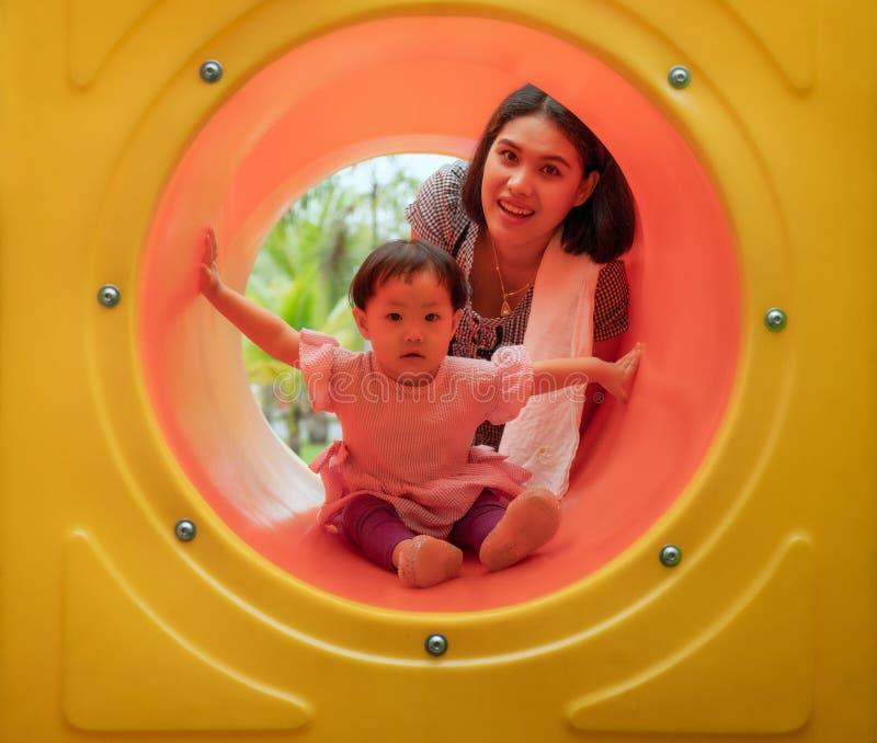 Den asiatiska modern och dottern är lycka och tycker om tillsammans i lekplats, med fullständigt lyckaögonblick royaltyfria bilder