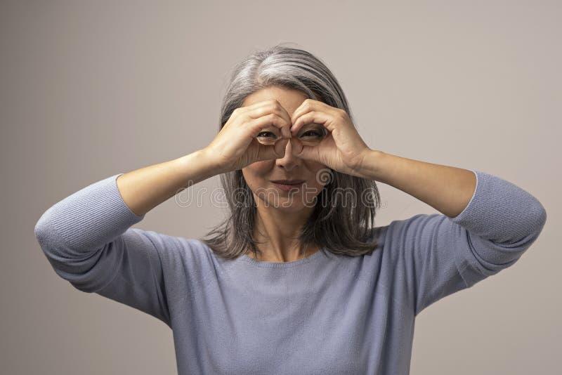 Den asiatiska mogna kvinnan gör ok gest som kikare fotografering för bildbyråer