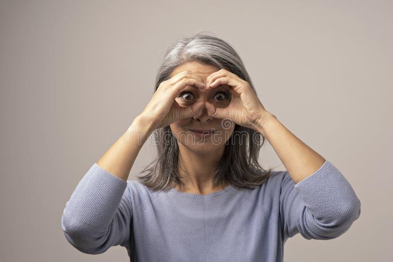 Den asiatiska mogna kvinnan gör ok gest som kikare arkivbilder