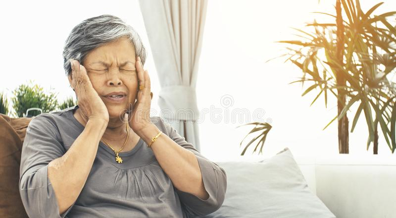 Den asiatiska mogna kvinnan med den äldre kvinnan med huvudvärk tar ett piller arkivfoton