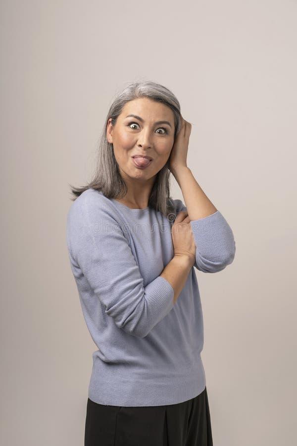 Den asiatiska mogna kvinnan visar tungan Stående arkivfoton