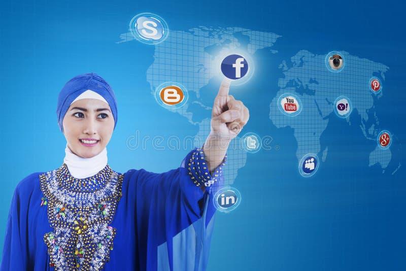 Den asiatiska muslimen förbinder till socialt massmedia på blått royaltyfri foto
