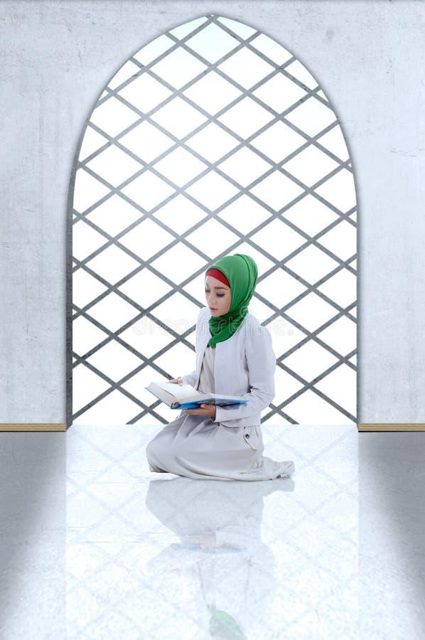 Den asiatiska muslimska kvinnan skyler sammanträde och läste in Koranen royaltyfria bilder