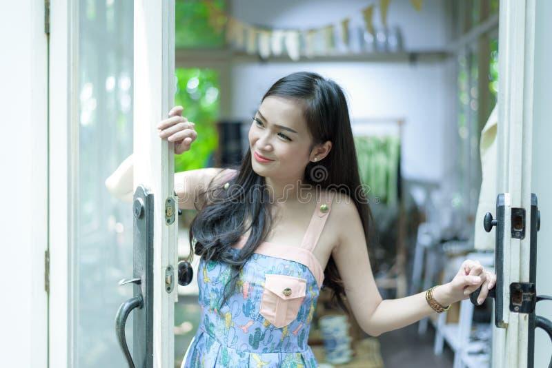 Den asiatiska nätta flickan har att öppna dörren med lyckligt och att le på det lilla trädträdgårdkafét, det Nakhon Pathom landsk arkivfoton