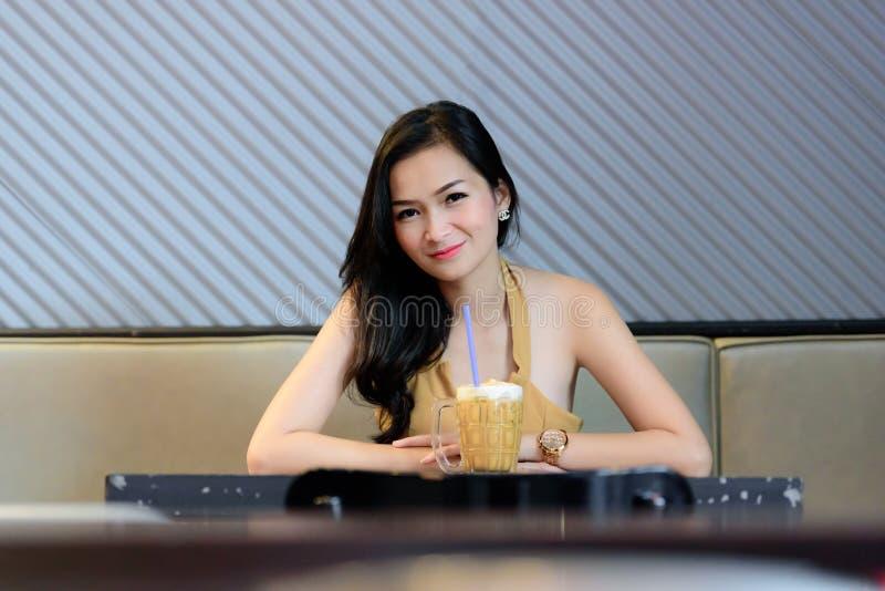 Den asiatiska nätta flickan har att koppla av med kaffe på kaffekaférestaurangen royaltyfri fotografi