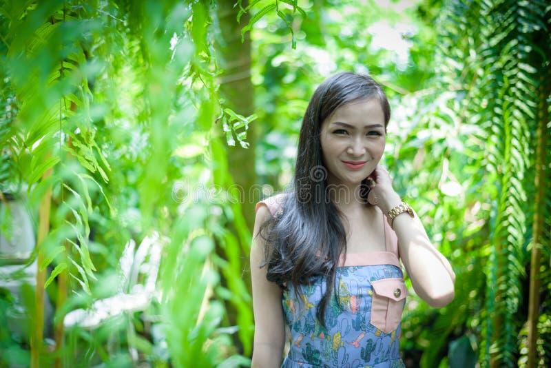 Den asiatiska nätta flickan har att koppla av med lyckligt och att le på det lilla trädträdgårdkafét, det Nakhon Pathom landskape fotografering för bildbyråer