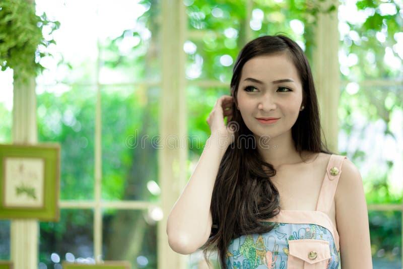 Den asiatiska nätta flickan har att koppla av med lyckligt och att le på det lilla trädträdgårdkafét, det Nakhon Pathom landskape arkivbild
