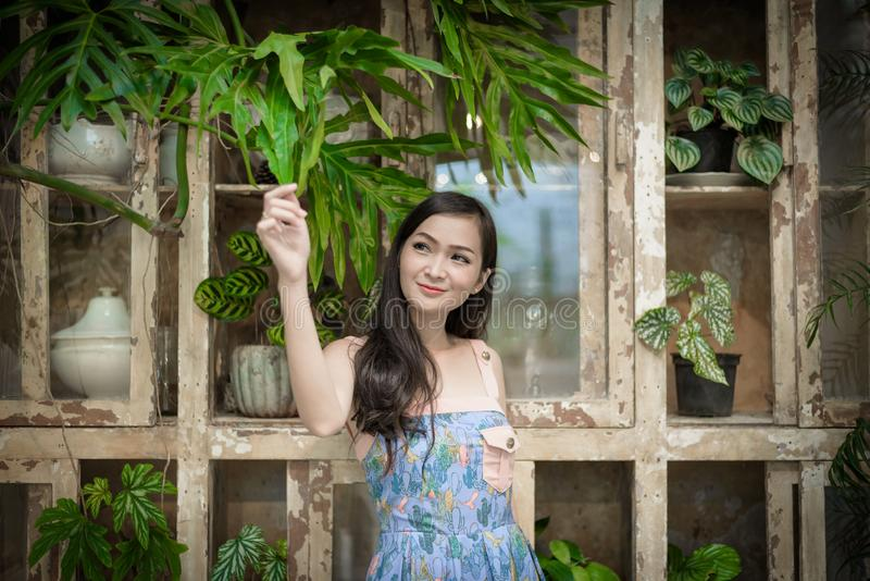 Den asiatiska nätta flickan har att koppla av med lyckligt och att le på det lilla trädträdgårdkafét, det Nakhon Pathom landskape royaltyfri foto