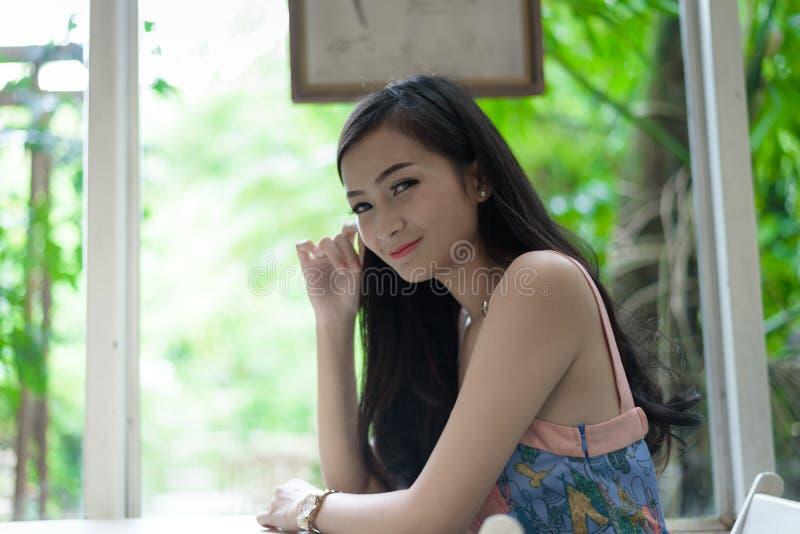 Den asiatiska nätta flickan har att koppla av med lyckligt och att le på det lilla trädträdgårdkafét, det Nakhon Pathom landskape royaltyfria foton
