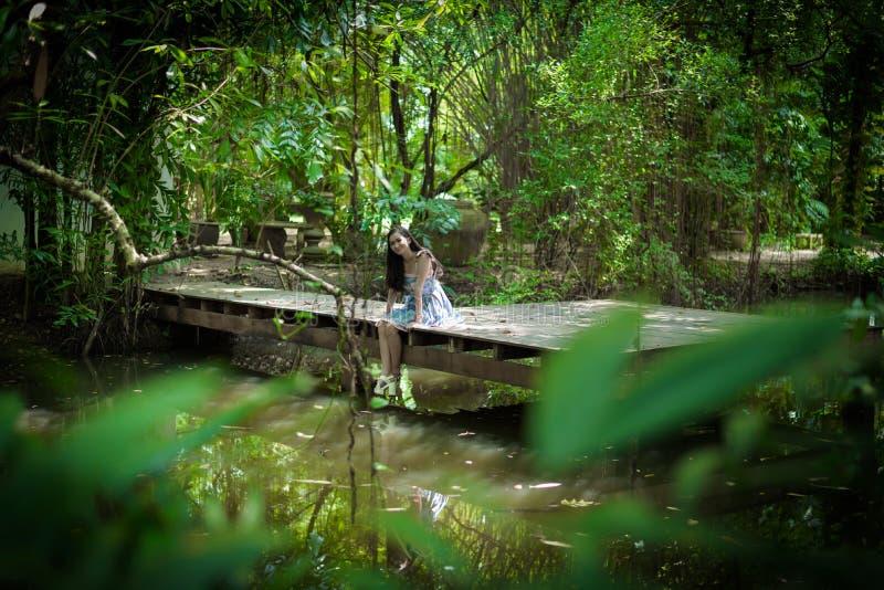 Den asiatiska nätta flickan har att koppla av med lyckligt och att le på det lilla trädträdgårdkafét, det Nakhon Pathom landskape royaltyfri bild
