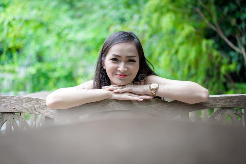 Den asiatiska nätta flickan har att sitta med lyckligt och att koppla av på det lilla trädträdgårdkafét, det Nakhon Pathom landsk arkivbild