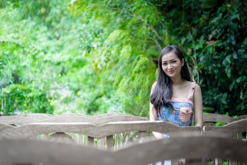 Den asiatiska nätta flickan har att sitta med lyckligt och att koppla av på det lilla trädträdgårdkafét, det Nakhon Pathom landsk royaltyfri foto