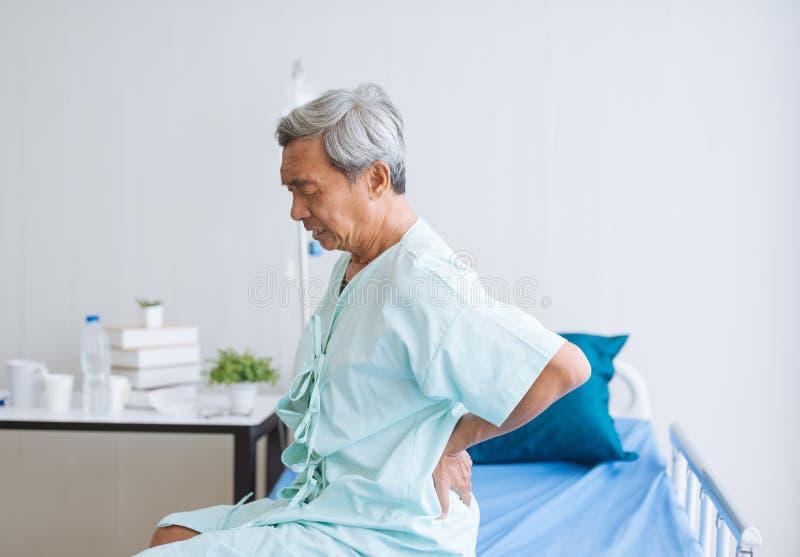 Den asiatiska patienten för den höga mannen smärtar, och ryggvärken vilar i sjukhus royaltyfri bild