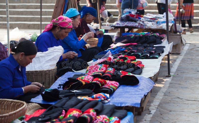 Den asiatiska pensionären anpassar sömnad och att sälja färgrika traditionella textilprodukter royaltyfri bild