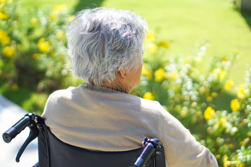 Den asiatiska pensionären eller den äldre kvinnapatienten för gammal dam på rullstolen parkerar in arkivfoto