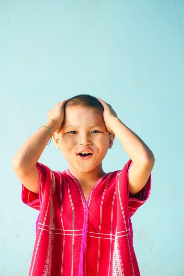 Den asiatiska pojken är huvudvärken på blå bakgrund arkivbilder