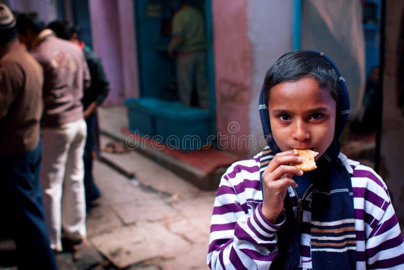 Den asiatiska pojken äter kakor på en kall afton i sten arkivbild