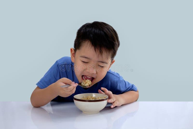 Den asiatiska pojken äter läckra ris och har en jätteglad framsida arkivfoto