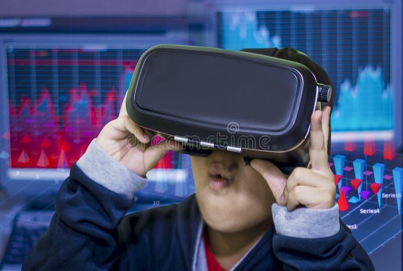 Den asiatiska pojken, bärande virtuell verklighetexponeringsglas på hans huvud, är upphetsad om vad han ser royaltyfri fotografi