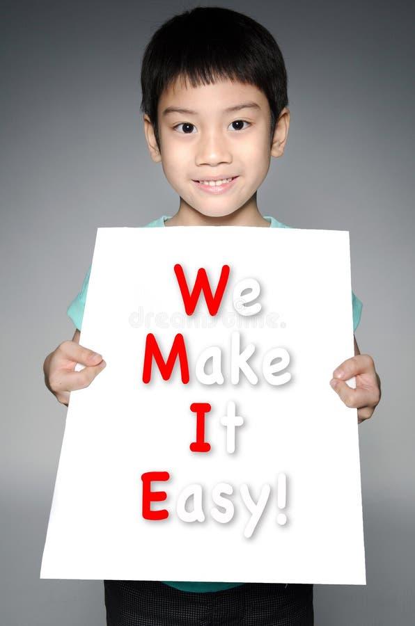 Den asiatiska pojken med GÖR VI IT LÄTT! meddelande på det vita brädet arkivbilder