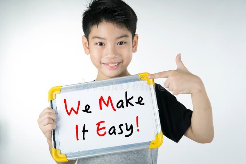 Den asiatiska pojken med GÖR VI IT LÄTT! meddelande på det vita brädet fotografering för bildbyråer