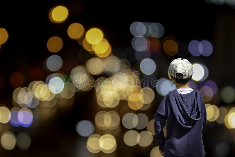 Den asiatiska pojken ser suddiga ljus av hus- och gataljuset, fängelse royaltyfri fotografi