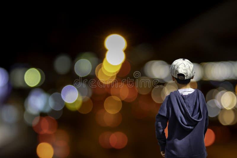 Den asiatiska pojken ser suddiga ljus av hus- och gataljuset, fängelse royaltyfri foto