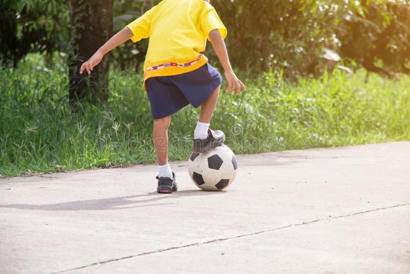 Den asiatiska pojken som spelar gammal fotboll på gatan, ungar spelar fotboll royaltyfri bild
