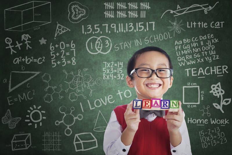 Den asiatiska pojkestudenthållen lär kvarteret i grupp royaltyfria foton