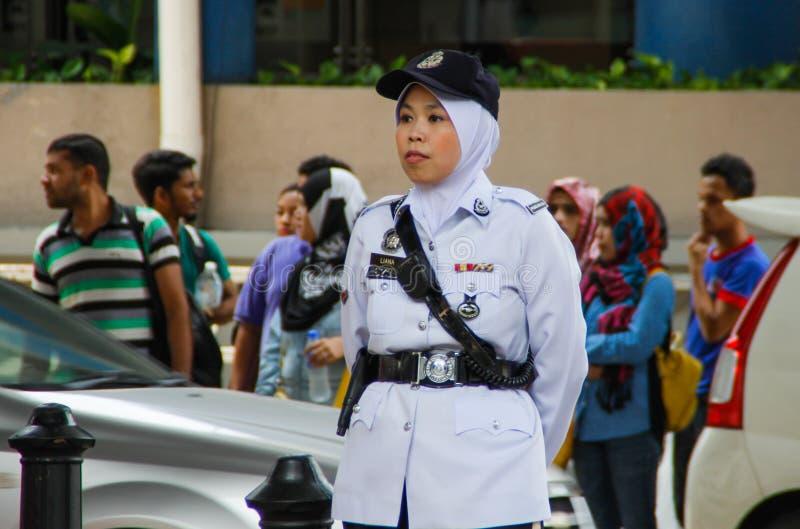 Den asiatiska poliskvinnan står längs vägen i en vit likformig, lock och hijab arkivbilder