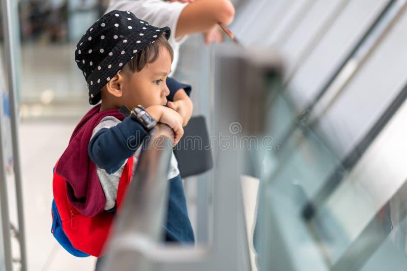 Den asiatiska pysen 3 gamla år bär väntande logi för påse till flyget i för flygplatstransport för port slutlig korridor royaltyfri foto
