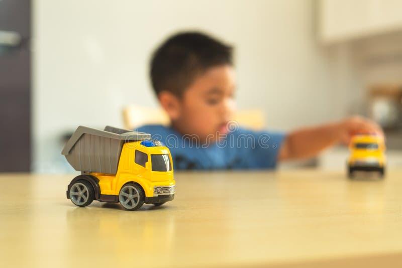 Den asiatiska pysen spelar med leksakbilar hemma arkivbild