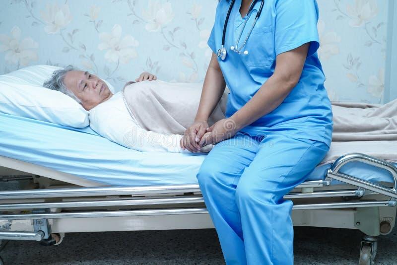 Den asiatiska sjuksköterskafysioterapeutdoktorn att att bry sig, hjälpa och stötta den höga eller äldre kvinnapatienten för den g royaltyfria foton