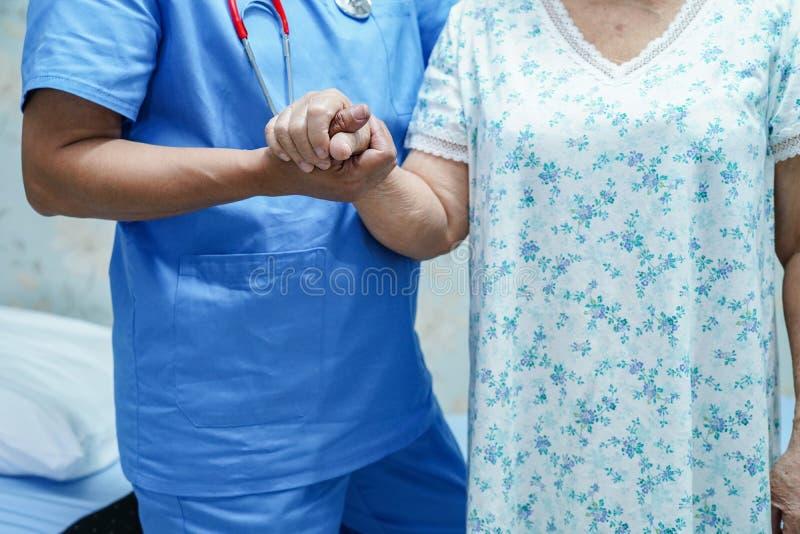 Den asiatiska sjuksköterskafysioterapeutdoktorn att att bry sig, hjälpa och stötta den höga eller äldre kvinnapatienten för den g arkivbild