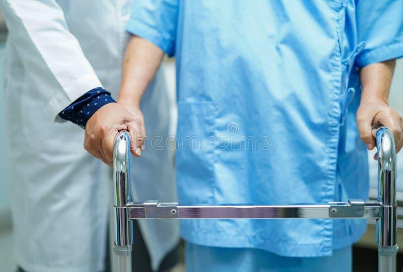 Den asiatiska sjuksköterskafysioterapeutdoktorn att att bry sig, hjälpa och stötta den höga eller äldre kvinnapatienten för den g royaltyfri fotografi
