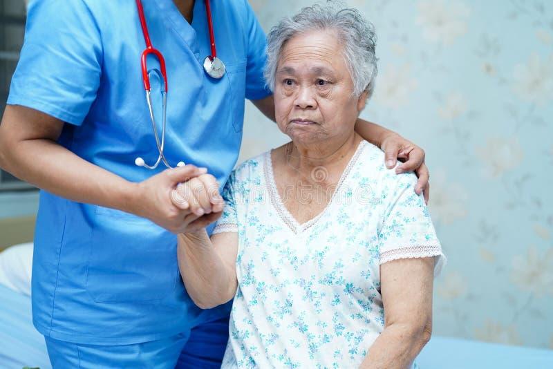 Den asiatiska sjuksk?terskafysioterapeutdoktorn att att bry sig, hj?lpa och st?tta den h?ga eller ?ldre kvinnapatienten f?r den g royaltyfria bilder
