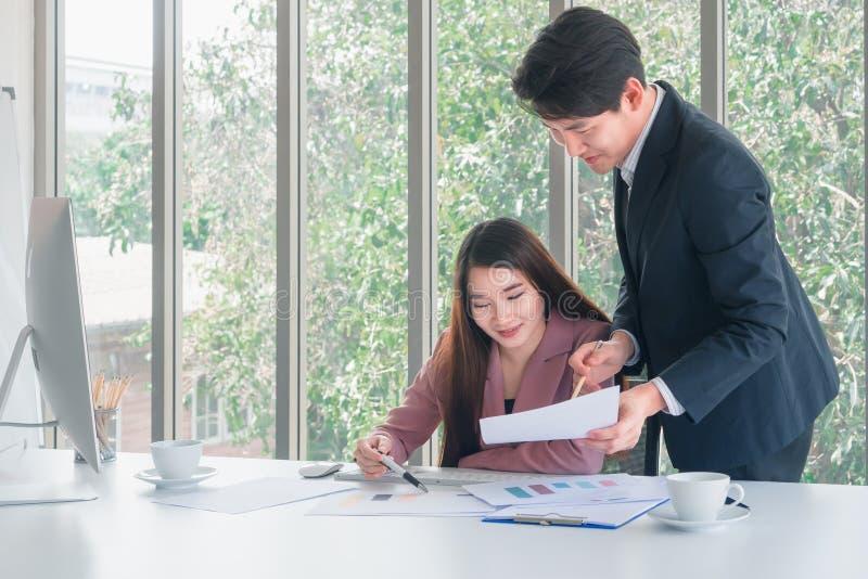 Den asiatiska stiliga affärsmannen i den marinblåa dräktställningen som förklarar jobbdetaljer till den härliga affärskvinnan för royaltyfri foto