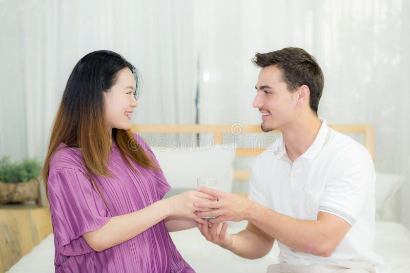 Den asiatiska stiliga maken tar omsorg om gravid kvinna med ger ett exponeringsglas av mjölkar royaltyfri fotografi