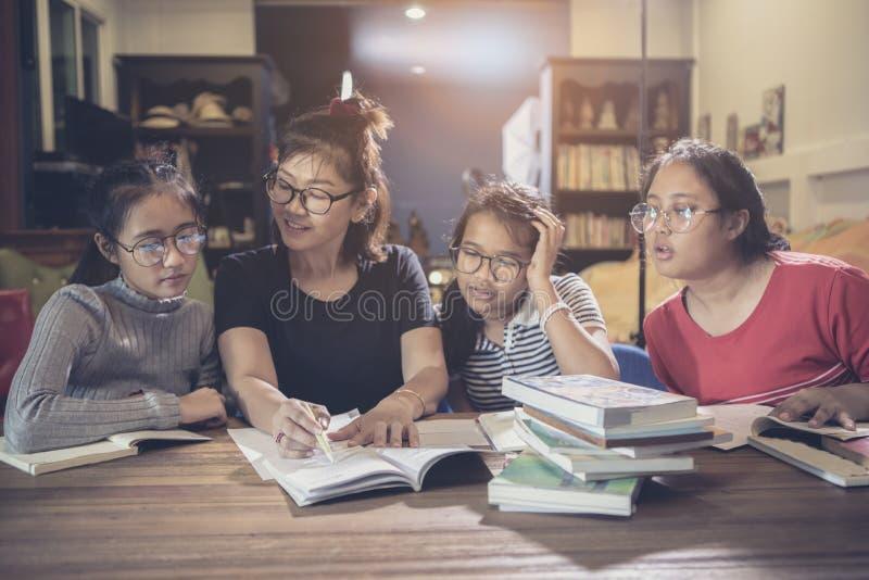 Den asiatiska studenten och läraren förklarar studiefallet i modern grupproo fotografering för bildbyråer