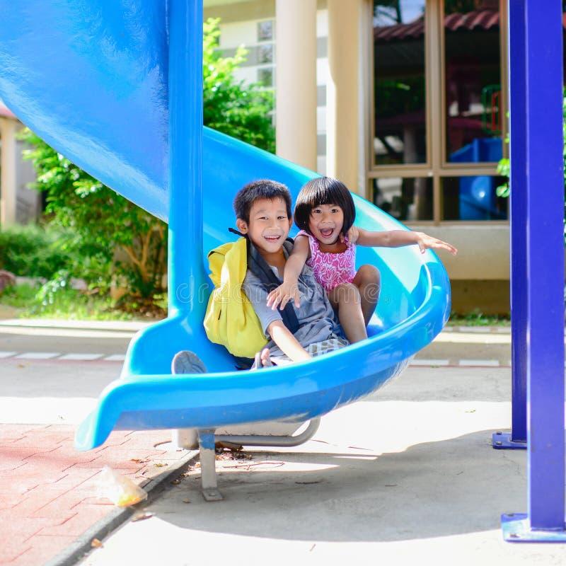 Den asiatiska syskongruppen tycker om lekplatsen fotografering för bildbyråer