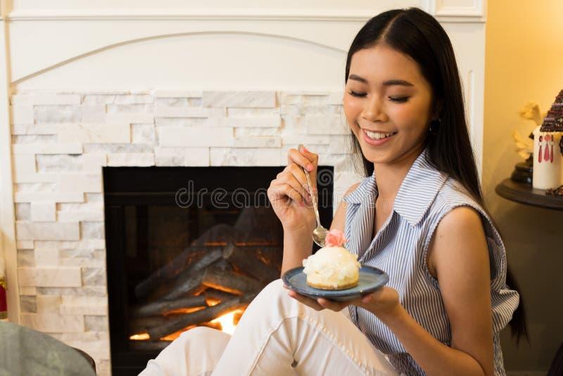 Den asiatiska systern tar fotosmak den läckra söta kakan royaltyfri foto